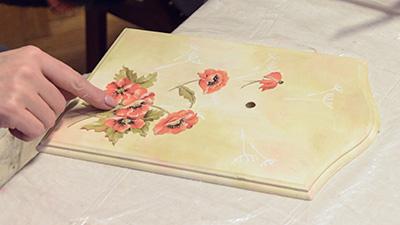 Przyklejanie motywu wyciętego z papieru do decoupage